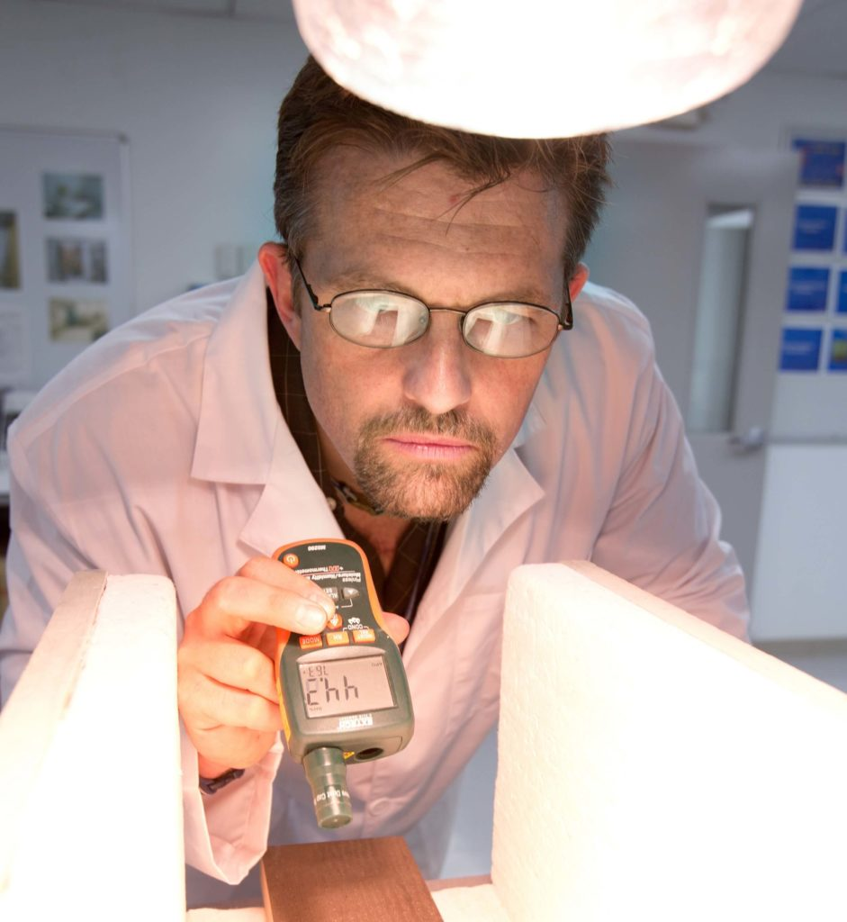 scientist looking at pvc window profile under bright light